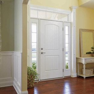 Inredning av en shabby chic-inspirerad mellanstor ingång och ytterdörr, med gula väggar, mörkt trägolv, en enkeldörr, en vit dörr och brunt golv