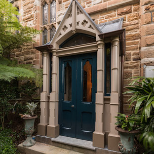 This is an example of a traditional front door in Sydney with brown walls, a double front door, a green front door and brown floor.