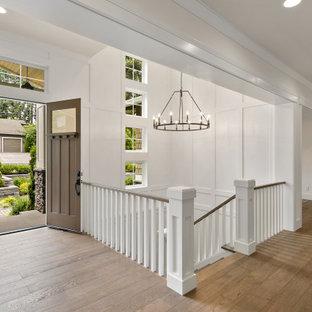Пример оригинального дизайна: большое фойе в стиле кантри с белыми стенами, паркетным полом среднего тона, двустворчатой входной дверью, входной дверью из дерева среднего тона, коричневым полом, многоуровневым потолком и панелями на стенах