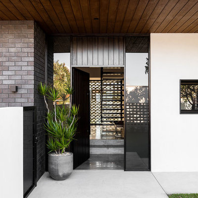 Trendy concrete floor and gray floor entryway photo in Perth with white walls and a black front door