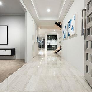 Foto de hall contemporáneo, grande, con paredes blancas, suelo de baldosas de porcelana, puerta simple y puerta blanca