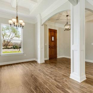 Cette photo montre un hall d'entrée chic avec sol en stratifié et une porte simple.