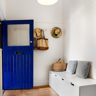 Photo of a contemporary foyer in Melbourne with white walls, medium hardwood floors, a single front door, a blue front door and brown floor.