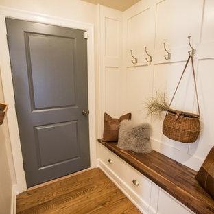 Idee per un piccolo ingresso o corridoio tradizionale con pareti beige, pavimento in legno massello medio, una porta singola e una porta grigia