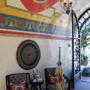 Esempio di un piccolo ingresso con vestibolo mediterraneo con pareti beige, pavimento in terracotta e una porta a due ante