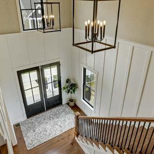Foto di un grande ingresso stile americano con pareti bianche, pavimento in legno massello medio, una porta singola, una porta marrone e boiserie