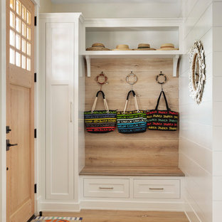 Entryway - coastal medium tone wood floor and brown floor entryway idea in Other with white walls and a medium wood front door