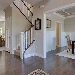 Example of a large classic medium tone wood floor entryway design in Other with beige walls