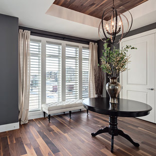Example of a mid-sized transitional painted wood floor entryway design in Calgary with gray walls and a white front door