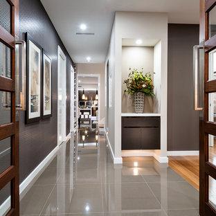 Immagine di un corridoio minimal di medie dimensioni con pareti con effetto metallico, pavimento in gres porcellanato, una porta a due ante, una porta in legno scuro e pavimento grigio