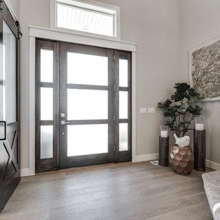 Cette photo montre une porte d'entrée craftsman de taille moyenne avec un mur beige, un sol en bois brun, une porte simple et une porte en bois brun.