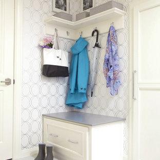 Klassisk inredning av en liten entré, med klinkergolv i porslin, vitt golv och vita väggar