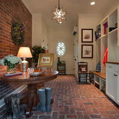 Country brick floor entryway photo in Other with white walls and a white front door