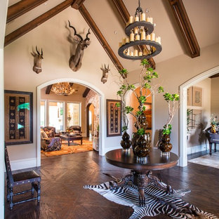 Large mountain style dark wood floor entryway photo in Dallas with beige walls and a dark wood front door
