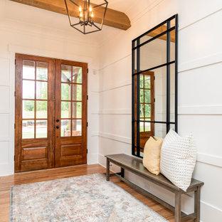 アトランタの中くらいの両開きドアカントリー風おしゃれな玄関ロビー (白い壁、無垢フローリング、木目調のドア、茶色い床、表し梁、羽目板の壁) の写真