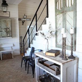 Cette photo montre une entrée romantique de taille moyenne avec un couloir, un mur blanc, un sol en brique et une porte en bois brun.