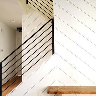 Ispirazione per un piccolo ingresso moderno con pareti bianche, parquet chiaro, una porta singola e pareti in perlinato