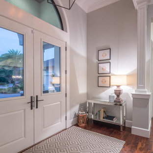 Coastal dark wood floor entryway photo in Tampa with gray walls and a white front door