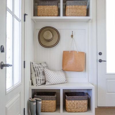 Mudroom - coastal medium tone wood floor mudroom idea in Jacksonville with white walls and a glass front door