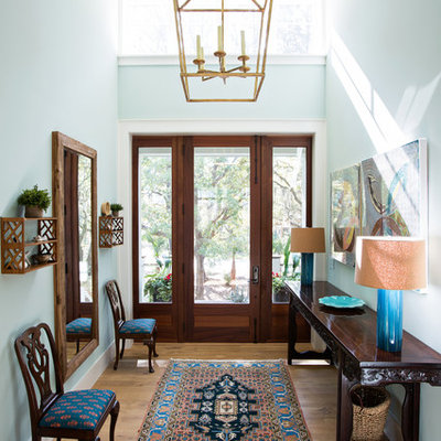 Entryway - mid-sized traditional medium tone wood floor and brown floor entryway idea in Charleston with blue walls and a glass front door