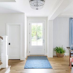 ミネアポリスの広い片開きドアビーチスタイルのおしゃれな玄関ロビー (白い壁、淡色無垢フローリング、白いドア、茶色い床) の写真