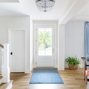 Inspiration for a large beach style light wood floor and brown floor entryway remodel in Minneapolis with white walls and a white front door