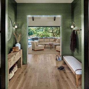 Lantlig inredning av en farstu, med gröna väggar, ljust trägolv, en dubbeldörr, en svart dörr och beiget golv