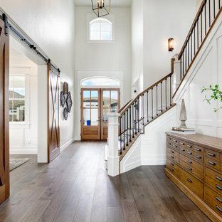 Klassisk inredning av en stor hall, med vita väggar, mellanmörkt trägolv, en dubbeldörr, mellanmörk trädörr och brunt golv