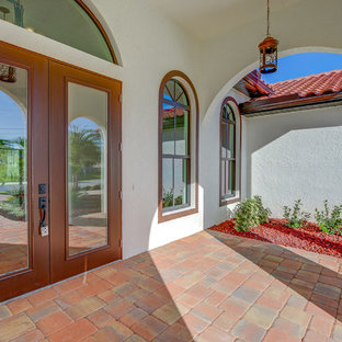Entryway - large mediterranean entryway idea in Other with beige walls and a brown front door