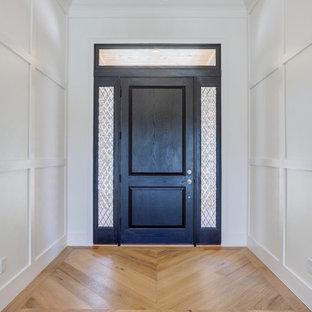 Diseño de puerta principal bandeja, tradicional renovada, grande, con paredes blancas, suelo de madera clara, puerta simple, puerta negra y suelo marrón