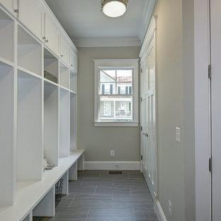 Cette image montre une grand entrée minimaliste avec un vestiaire, un mur gris et un sol en linoléum.