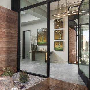 ラスベガスの中くらいの回転式ドアコンテンポラリースタイルのおしゃれな玄関ロビー (グレーの壁、磁器タイルの床、ガラスドア、グレーの床) の写真