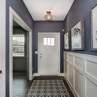 Inspiration för en mellanstor amerikansk hall, med en enkeldörr, en vit dörr och mörkt trägolv