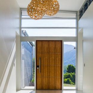 ケアンズの中くらいの回転式ドアコンテンポラリースタイルのおしゃれな玄関ロビー (白い壁、磁器タイルの床、木目調のドア、黄色い床) の写真