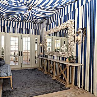 Aménagement d'une grand entrée exotique avec un couloir, un mur multicolore, moquette, une porte double, une porte blanche et un sol bleu.