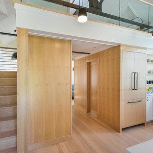 Idéer för små industriella hallar, med vita väggar, ljust trägolv, en pivotdörr, mellanmörk trädörr och beiget golv