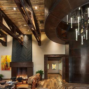 На фото: класса люкс огромные фойе с серебряными стенами, паркетным полом среднего тона, поворотной входной дверью и металлической входной дверью