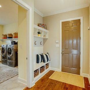 Inspiration pour un vestibule traditionnel de taille moyenne avec un mur beige, une porte simple, une porte marron, un sol en bois brun et un sol marron.