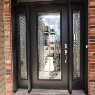 Cette photo montre une porte d'entrée chic de taille moyenne avec un mur beige, béton au sol, une porte simple et une porte noire.