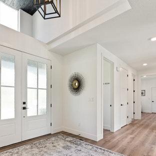 Modern inredning av en stor foajé, med vita väggar, laminatgolv, en dubbeldörr, en vit dörr och brunt golv