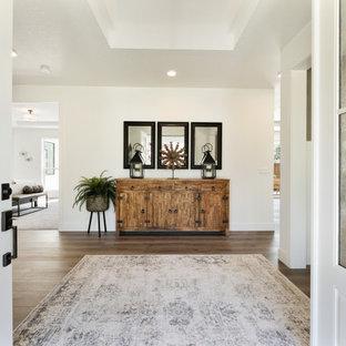 Idee per un grande ingresso contemporaneo con pareti bianche, pavimento in laminato, una porta a due ante, una porta bianca, pavimento marrone e soffitto a cassettoni
