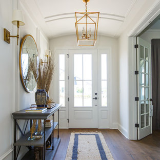 Example of a coastal medium tone wood floor entryway design in Jacksonville with white walls and a white front door
