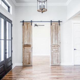 Cette image montre un grand hall d'entrée rustique avec un mur blanc, un sol en bois brun, une porte double, une porte en verre et un sol marron.