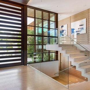 Foto di un ingresso o corridoio design con pareti beige, una porta singola, una porta in legno scuro, pavimento beige e pareti in legno