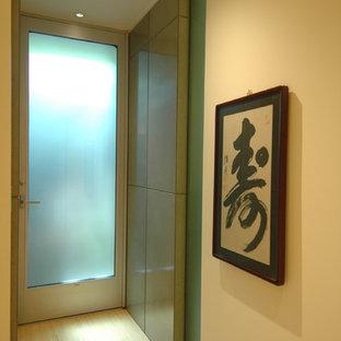 Cette image montre un petit vestibule minimaliste avec un mur jaune, un sol en bambou, une porte simple et une porte en verre.