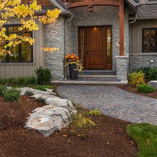 Idée de décoration pour une entrée chalet de taille moyenne avec un mur gris, une porte simple et une porte en bois brun.