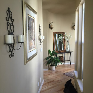 Example of a small tuscan light wood floor entryway design in Boise with beige walls