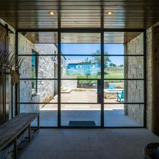 Exemple d'un hall d'entrée nature de taille moyenne avec un mur blanc, béton au sol, une porte pivot, une porte en verre et un sol blanc.
