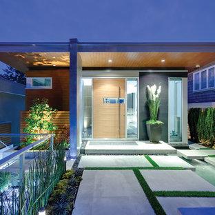 На фото: прихожая в современном стиле с поворотной входной дверью и входной дверью из дерева среднего тона