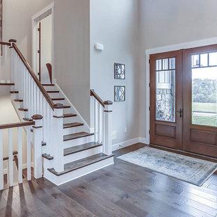 Aménagement d'un très grand hall d'entrée campagne avec un mur gris, un sol en bois brun, une porte double et une porte en bois brun.